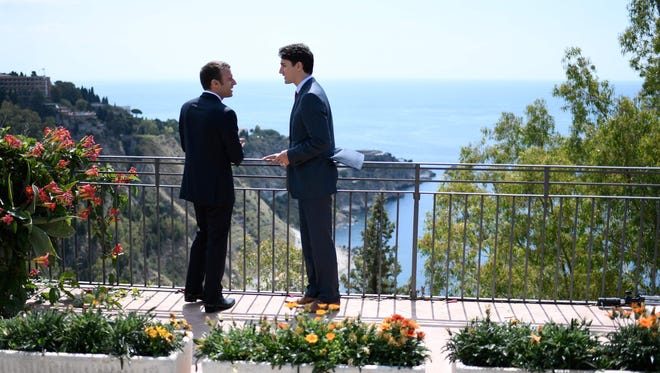 Canadian Prime Minister Justin Trudeau and French President Emmanuel Macron talk as they attend the Summit of the Heads of State and of Government of the G7, the group of most industrialized economies, plus the European Union in Taormina, Sicily.