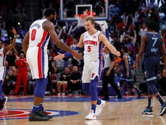 Luke Kennard (5) celebrates a three-point basket with Andre Drummond.