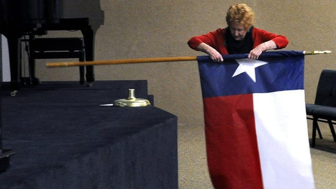 Ronald W. Erdrich/Reporter-News Grace Hefner, a member of the Brown County Republican Women, rolls up a Texas flag during the Feb. 4 candidate forum sponsored by the group in Brownwood.