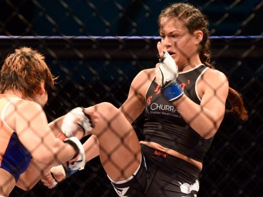 Brogan Walker lands a front thrust kick to the midsection of Emiko Raika in a 125-pound fight at PXC 50 at the UOG Calvo Field House on Dec. 4. The kick sent Raika reeling backward into the cage, where Walker was able to control the remainder of the round and help secure a unanimous decision.
