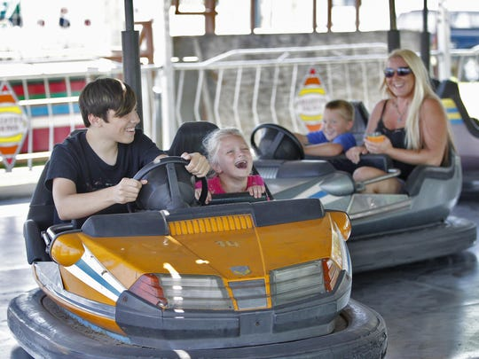 Kaleb Benedict, 14, left, drives his sister Kali, 5, as they try to avoid getting bumped from his brother Dominic, 4, and his mom Lyndsey Klees at 2017's Broome County Fair.