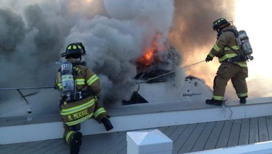 Barnegat firefighters battle a boat fire at the Barnegat docks on Sunday.