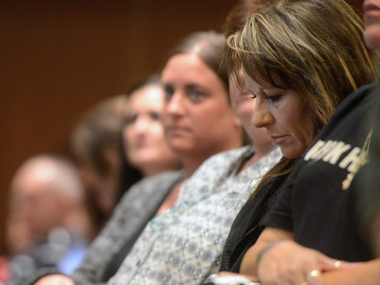 Tami Darby, mother of Rise Together co-founder and former addict Douglas Darby, looks away as Bridgette Henschel (not pictured) shares the story of losing her daughter Amalia 'Molly' Henschel to heroin, while presenting at the 'It Doesn't Start With Heroin' Summit.