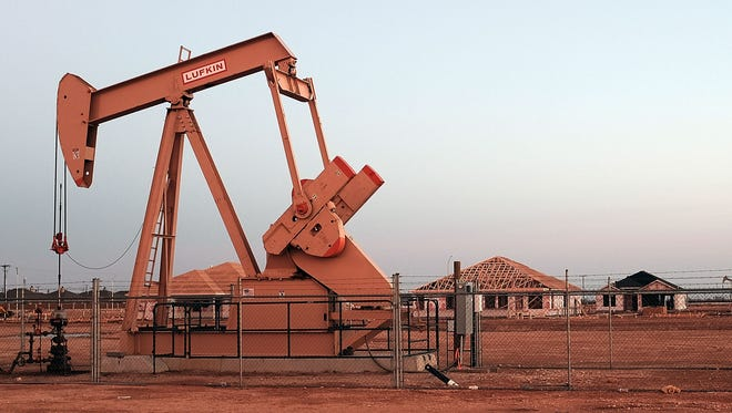 An oil well is viewed near a construction site for homes on February 5, 2015 in Midland, Texas.