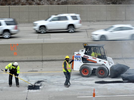 Road workers repair the road surface on eastbound 696