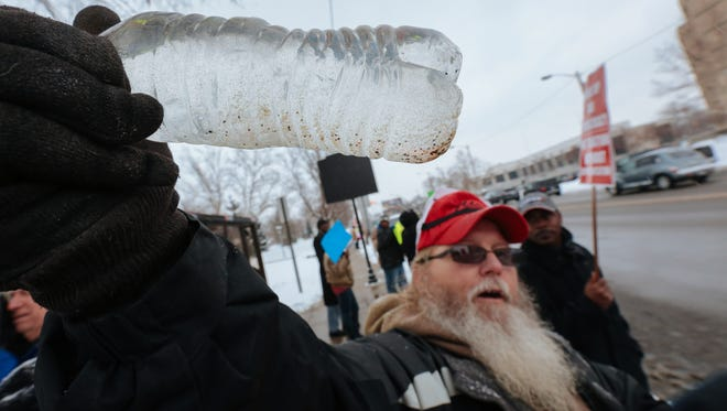 Tony Pallaeeno Jr. holds a sample of water he boiled water from his house including a sand deposit and iron, while protesting the quality of water in front of Flint City Hall on Wednesday January 21, 2015 in downtown Flint.