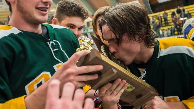 The BFA St. Albans boys hockey team celebrates their D1  Vermont State Championship Thursday night at UVM, defeating Spaulding 2-1.