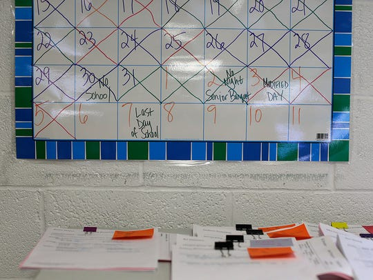 A calendar hangs on the wall inside the classroom at
