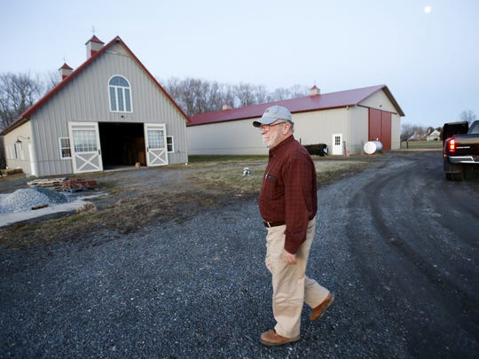 Farm owner Gary Warren walks among the out buildings of his Port Penn property last year.