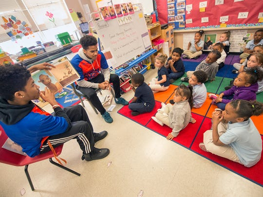 Jayden Handy, left, and Jacquez Casiano read a story to a Pre-K class at Devers K-8 school in York. The William Penn seniors, on the basketball team, plan on attending Shippensburg University.