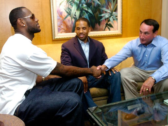 NBA basketball star LeBron James, left, shakes hands