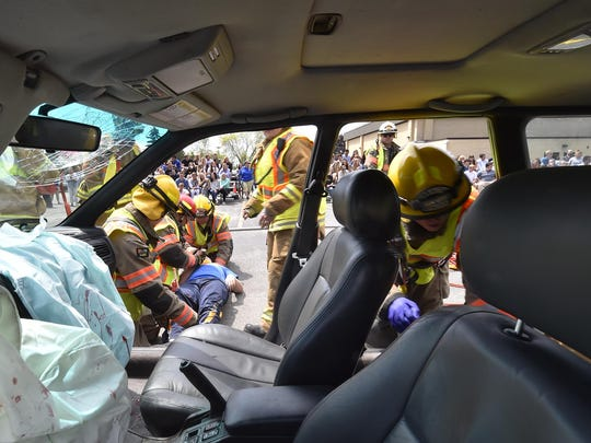 Fire and rescue personnel lift a Gibraltar High School student on a gurney after a mock crash involving two-cars and implying drinking and driving as the cause of the fatality Thursday at the high school. The drill was held behind the school.