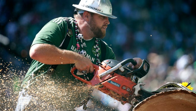 "Joey Webber, also known as ""Timber Joey,"" cuts a section of the log he cuts with a chain saw after every Portland Timbers goal, during an MLS soccer match against the Seattle Sounders, Sunday, Aug. 28, 2016, in Portland, Ore."