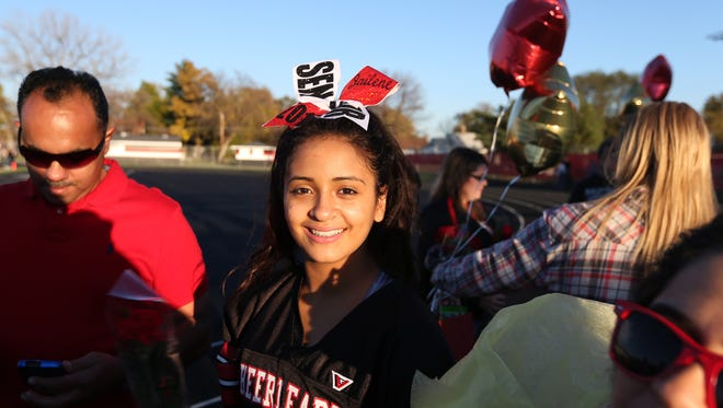 Des Moines East senior cheerleader Jailene Rodriguez waits to be escorted by her parents, Omar and Milda, on senior night at Williams Metro Stadium in Des Moines.