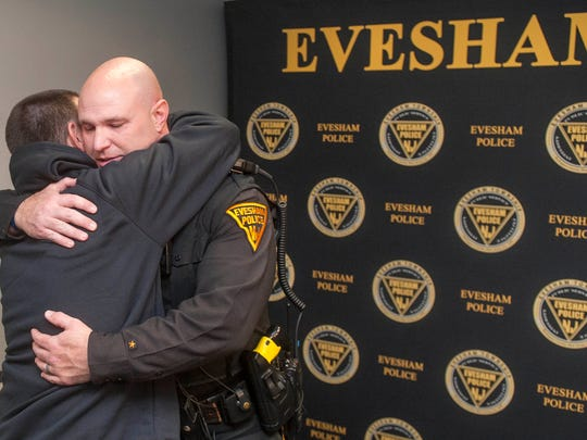 Evesham Police Officer Brian Strockbine, right, is hugged by Peter Corelli of Marlton as Corelli visited the Evesham police station to thank Officer Strockbine for saving his mother's life,  after she was allegedly left unconscious and not breathing after a physical assault by her husband in Evesham last month.  Officer Strockbine also saved the lives of two others recently and was named the Officer of the Month by the Evesham Police Department.  04.08.16