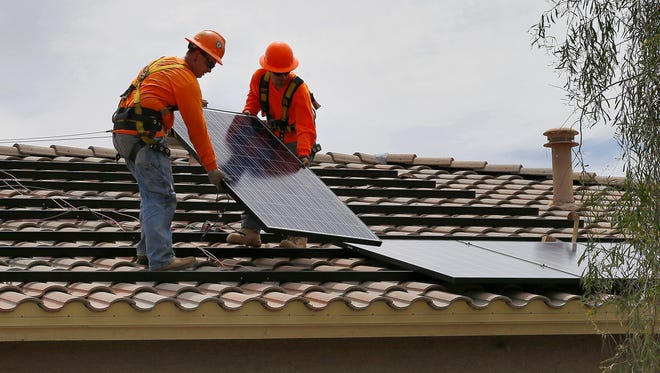 Electricians install solar panels on the roof of a Goodyear home.