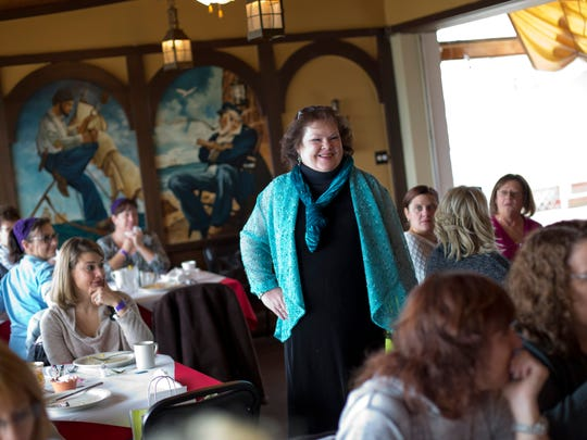 Marcy Miller, of Burtchville Township, shows off clothing from a local store during breakfast and a fashion show as part of the Girlfriend's Getaway Weekend Saturday, November 14, 2015 at The Windjammer in Lexington.