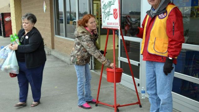 Morganfield Lions Club member David Presser, right, manned the Salvation Army kettle on Christmas Eve. The Lions Club is one of many civic groups and churches that volunteered to ring the Salvation Army bell this year.
