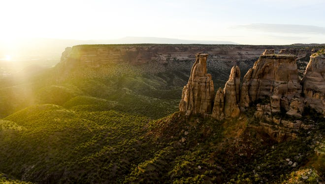 Colorado National Monument near Grand Junction features stunning views of rock spires. COLORADOAN LIBRARY The sun rises over Colorado National Monument Wednesday, July 15, 2015, near Grand Junction, CO.
