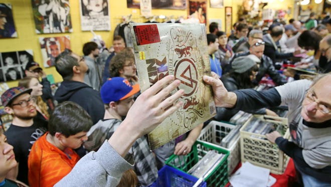 Rick Simpson, right, a DJ at WRUR-FM (88.5), hands off a Linkin Park album to a shopper during Record Store Day at Record Archive last year.