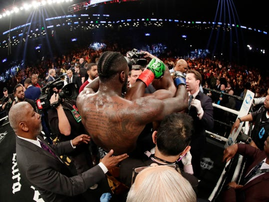 Deontay Wilder, back to camera, hugs Luis Ortiz after the WBC heavyweight championship bout Saturday, March 3, 2018, in New York. Wilder won in the 10th round. (AP Photo/Frank Franklin II)