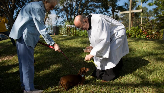 The Rev. Bill Faupel of St. Paul's Episcopal Church blesses Hazel, a dachshund, during the church's annual Blessing of the Animals service Saturday, Nov. 25, 2017, in Naples.