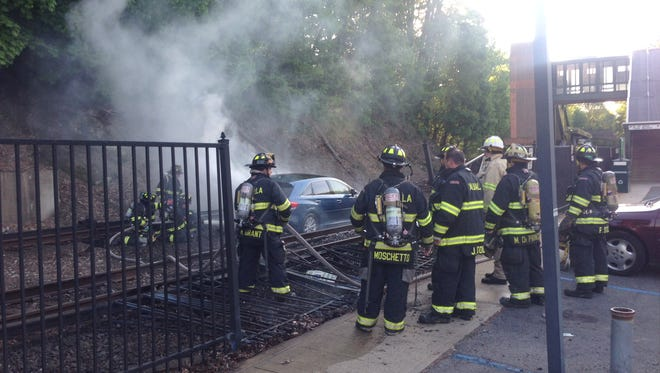 Firefighters at the scene of a car fire on the tracks at the Valhalla train station.
