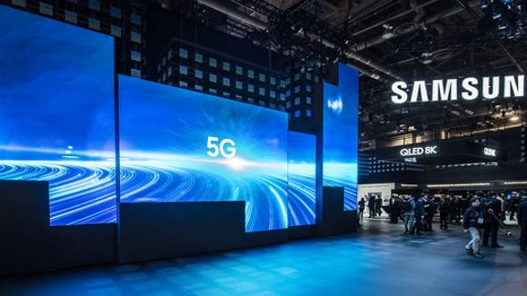 "A Samsung showcase with TVs that read ""5G"" on them."
