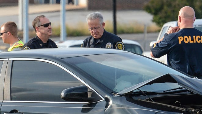 Anderson police Chief Jim Stewart, left, Capt. Mike Walters, and Capt. Michael Bracone, right, at the scene of an accident with a police car and other vehicles in downtown Anderson Thursday evening.