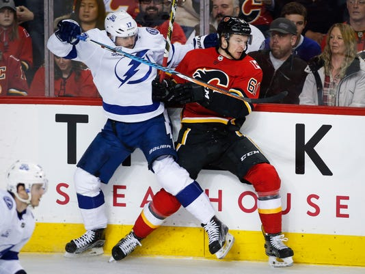 Tampa Bay Lightning's Alex Killorn, left, checks Calgary Flames' Brett Kulak during the second period of an NHL hockey game Thursday, Feb. 1, 2018, in Calgary, Alberta. (Jeff McIntosh/The Canadian Press via AP)