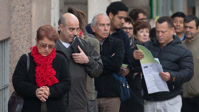 Unemployed people line up outside a government unemployment office in Madrid in October 2013.