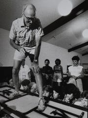 Verne Rockcastle stands on a table at a conference of science teachers in July 1988 as the teachers blow through straws into plastic bags taped to the table and and lift him.