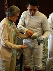 Cameron Silver, 17, shows the proper grip of his fencing sword to Arlington resident Fran Schroeter.