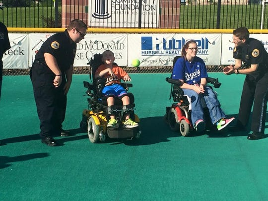 Police, firefighters, local high school teams and scores of others help each Miracle League game get off. Des Moines police officers assist players with a 2015 game.