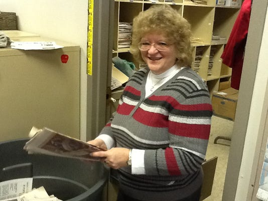 Nancy Myers cleans out some of her many files Friday after 37 years at The Evening Sun.