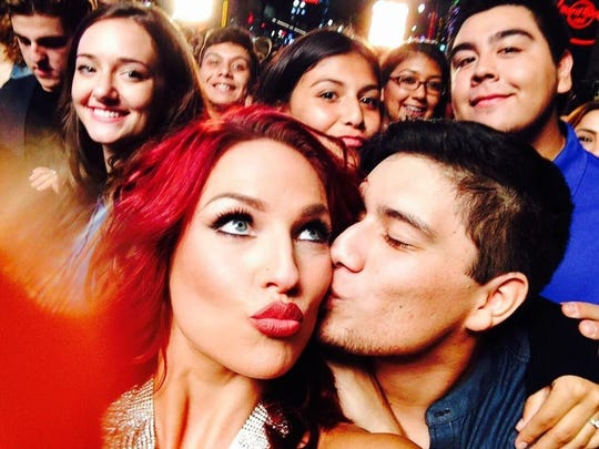 """Santiago Ocampo, a member of the Coachella Valley High School Dance Team, kisses professional dancer Sharna Burgess during the filming of the """"Dancing With the Stars"""" opening scene. The show premieres Monday."""