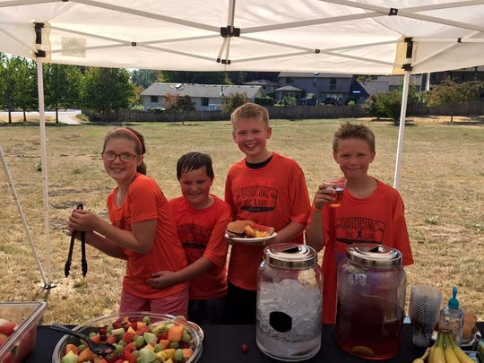 """Olivia Weiland (from left), Kaden Vincent, Logan Matot and Cole Weiland enjoy a healthy barbecue donated by Adam's Ribs during """"Bridging the Gap Salem Leadership Foundation 10K."""""""