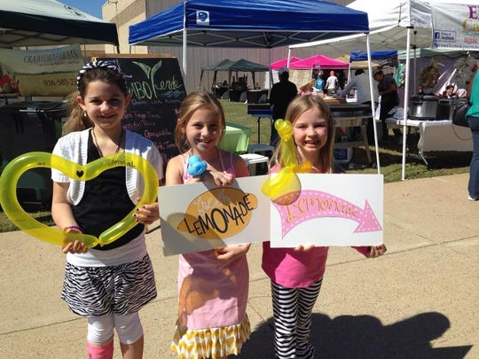 Kids hold signs for a lemonade stand at Bossier Farmer's