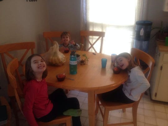 The Bennett siblings enjoying homemade snow cones are, clockwise from top, Aaron, Lydia and Sarah.