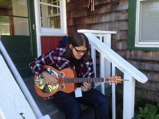 """Hub """"Hub Cub"""" Chason, 15, practices slide guitar on his Dobro on the second day of the Roots Rock Revival music camp in the Catskill Mountains."""