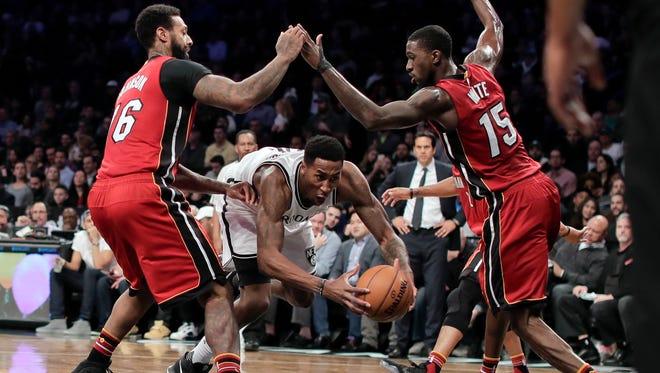 Nets forward Rondae Hollis-Jefferson tries to split the defense of Miami Heat forward James Johnson (16) and forward Okaro White (15) during the third quarter of a game  Wednesday, Jan. 25, 2017, in New York. The Heat won 109-106.