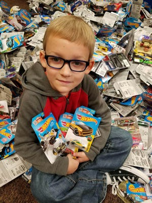 Jackson Smith, 6, sits among the Hot Wheels cars his classmates at Tri Elementary School helped collect. Smith and his mother, Allison, started donating Hot Wheels to Riley Children's Hospital after Jackson finished his own rounds of chemotherapy.
