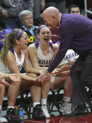 Indianola girls' basketball coach Bert Hanson celebrates with Maddie Post and Rachel Bishop during the final seconds of a Class 5A state quarterfinal victory in 2017.
