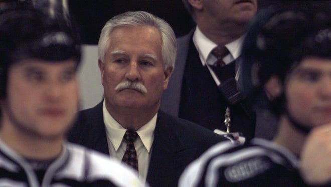 Michigan State hockey coach Ron Mason watches as Michigan is presented with the CCHA tournament championship trophy in March 2002.