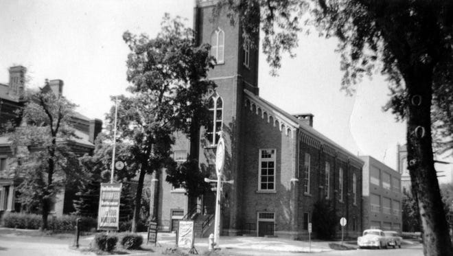 Old St. Joseph's Church, 1950s. Built in 1857, St. Joseph's first brick church, which stood on the NW corner of Croghan and Clover Street, is seen here in its last years.  The original section of the high school has already been built on Clover Street, and it would soon be extended all the way to Croghan, replacing the old church and the former rectory that stood next door.  The roof of the 1908 school on the corner of Wood Street appears at the left.  A gas station in the foreground was on the SW corner at the time.