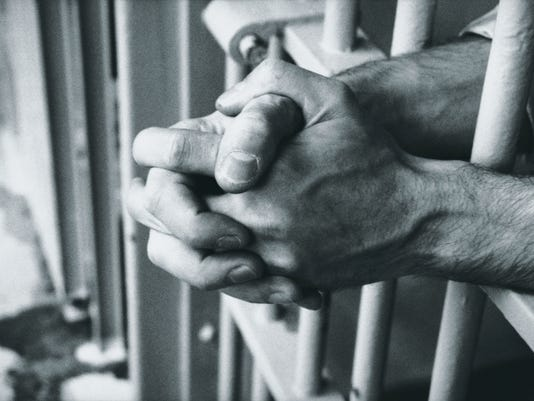 Prison bars with hands