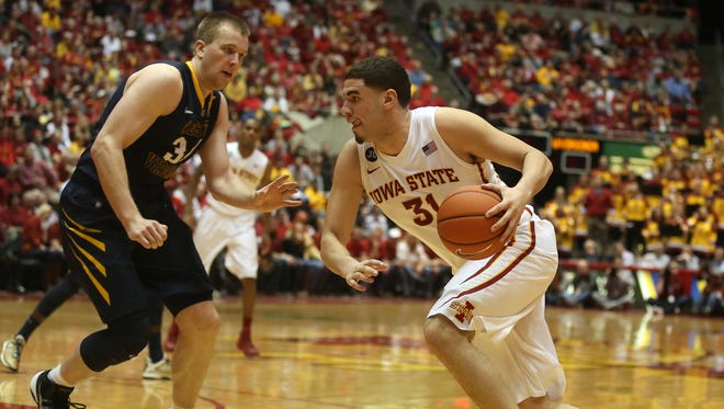 Iowa State forward Georges Niang moves the ball inside against West Virginia's Kevin Noreen at Hilton Coliseum in Ames on Tuesday, Feb. 26, 2014.