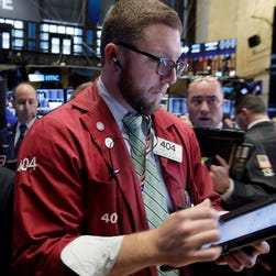 Trader Ryan Falvey, center, works on the floor of the New York Stock Exchange, Friday, Nov. 13, 2015.