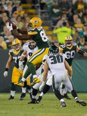 Green Bay Packers tight end Kennard Backman (86) makes a leaping catch in front of Philadelphia Eagles  safety Ed Reynolds (30) in the fourth third quarter during their preseason game at Lambeau Field.