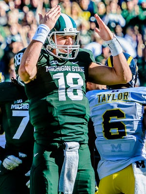 MSU quarterback Connor Cook pumps up the crowd after running to the Michigan 4 yard line on a quarterback keeper early in the 1st quarter of their game in 2014.